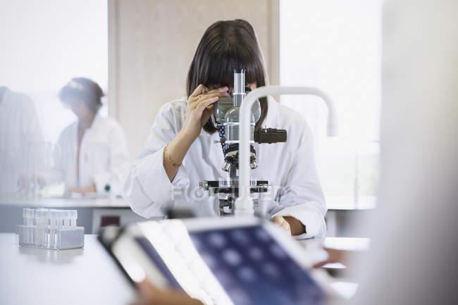Female college student using microscope in science laboratory classroom — Stock Photo