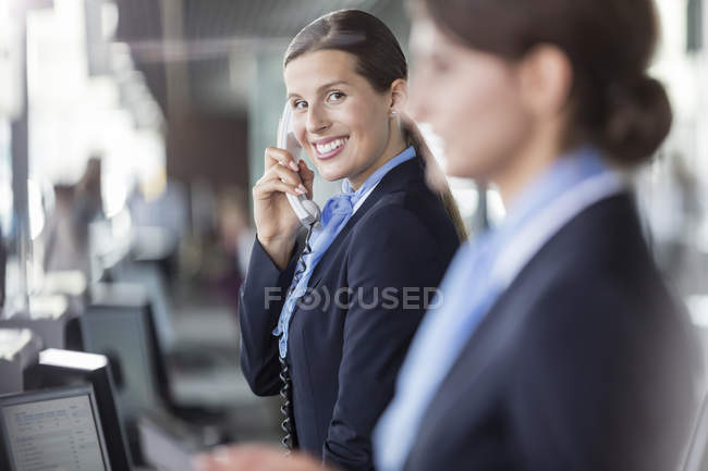 Portrait smiling customer representative talking on telephone at airport check-in counter — Stock Photo