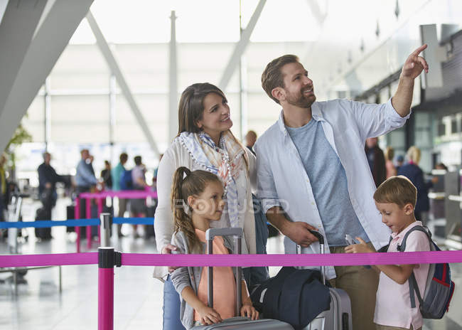 Family with suitcases pointing in airport concourse — Stock Photo
