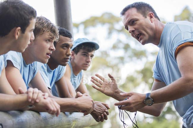 Chef d'équipe motivant l'équipe au camp d'entraînement parcours d'obstacles — Photo de stock