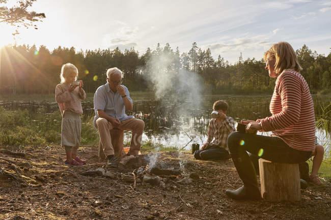 Бабушки и внуки наслаждаются костром на солнечном берегу — стоковое фото