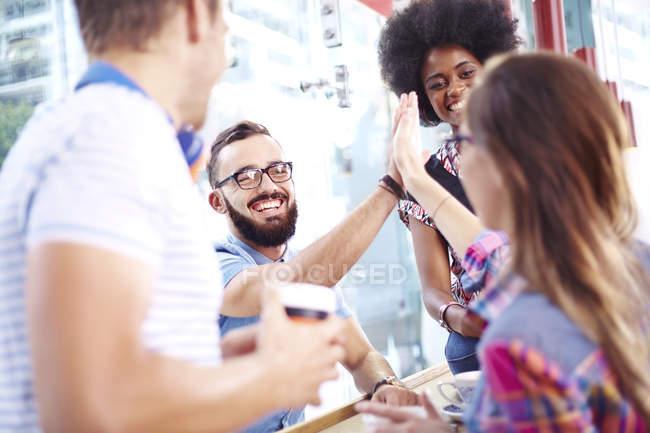 Amici che danno alta fiving nella moderna caffetteria — Foto stock