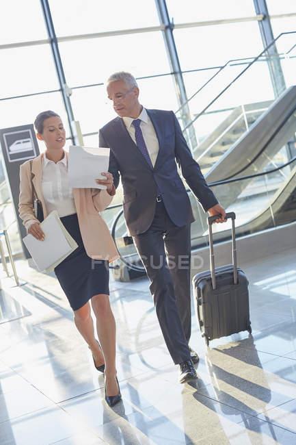 Uomini d'affari che discutono di scartoffie in aeroporto — Foto stock