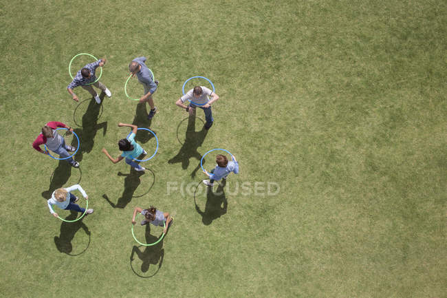 People spinning in plastic hoops in sunny grass — Stock Photo