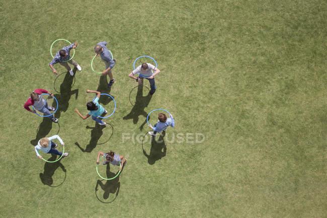 Les gens filant dans des cerceaux en plastique dans l'herbe ensoleillée — Photo de stock
