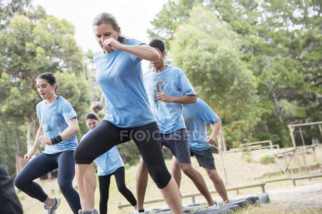 Решительные люди, прыгающие на шинах на полосе препятствий в учебном лагере — стоковое фото