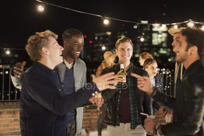 Giovani uomini che bevono e ridono alla festa sul tetto — Foto stock