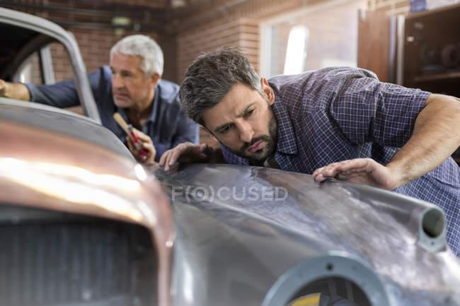 Целенаправленные механик, изучения классических автомобилей группы в Мастерские авторемонтные — стоковое фото