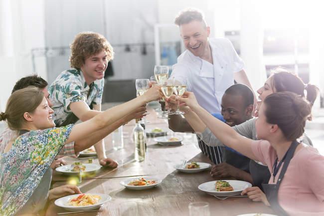 Lo chef insegnante ed allievi tostatura bicchieri di vino in cucina ...