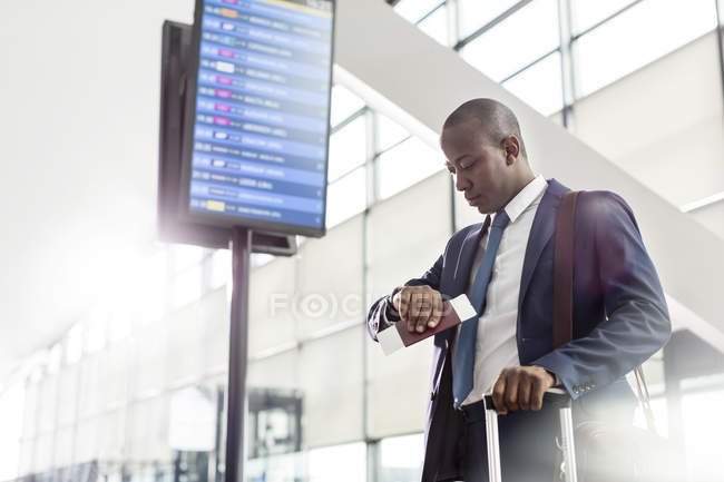 Businessman checking the time on wristwatch below arrival departure board at airport — Stock Photo