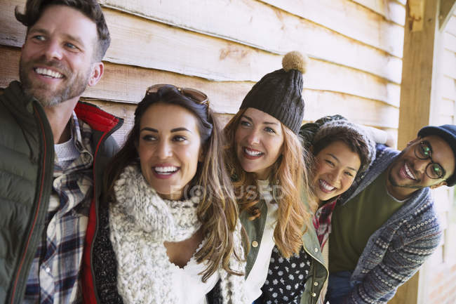Smiling friends standing in a row outside cabin — Stock Photo