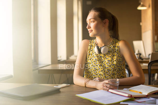 Pensive casual businesswoman with headphones looking away in office — Stock Photo