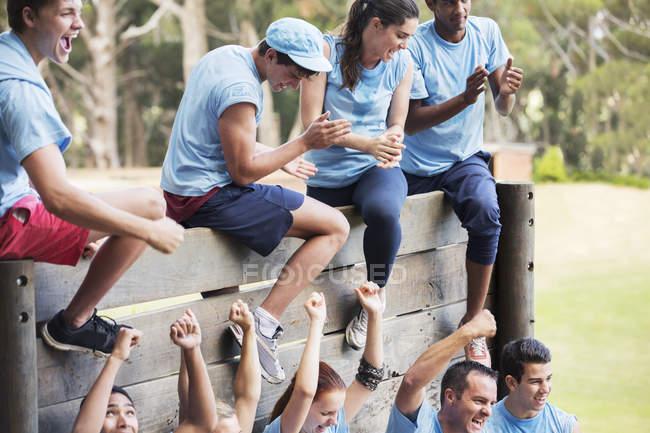 Jubelnde Mannschaft an Mauer auf Boot-Camp-Hindernisparcours — Stockfoto