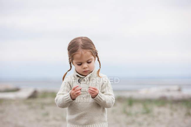 Цікаво дівчина вивчення Галька на пляжі — стокове фото