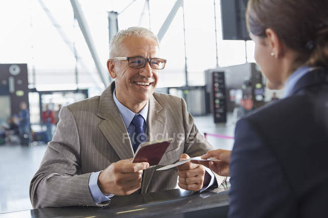 Smiling businessman giving passport to customer service representative at airport check-in counter — Stock Photo