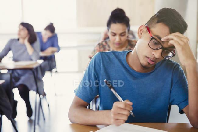 Ernsthafte männliche College-Student Abnahme Test am Schreibtisch im Klassenzimmer — Stockfoto