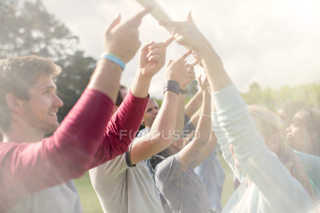 Team balancing pole overhead with fingertips — Stock Photo