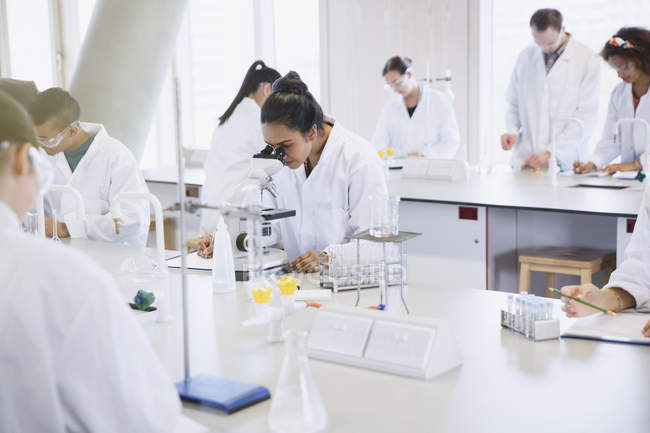 College students using microscope conducting scientific experiment in laboratory — Stock Photo