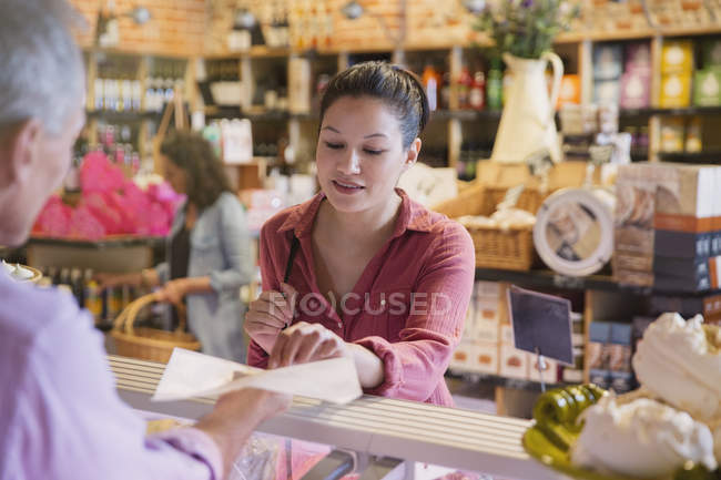 Woman sampling cheese at deli counter in market — Stock Photo