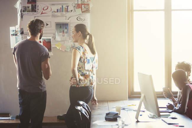 Creativi uomini d'affari che rivedono bozze e appunti sulla parete dell'ufficio — Foto stock