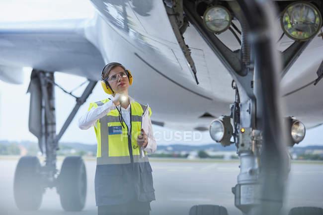 Рабочих местах экипажа под самолет с фонариком на асфальт аэропорта — стоковое фото