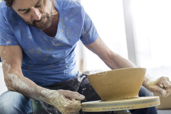 Mature man using pottery wheel in studio — Stock Photo