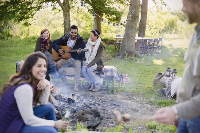Friends hanging out playing guitar at campfire — Stock Photo