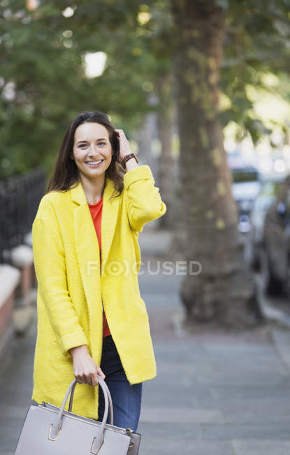 Portrait smiling mature woman on sidewalk — Stock Photo