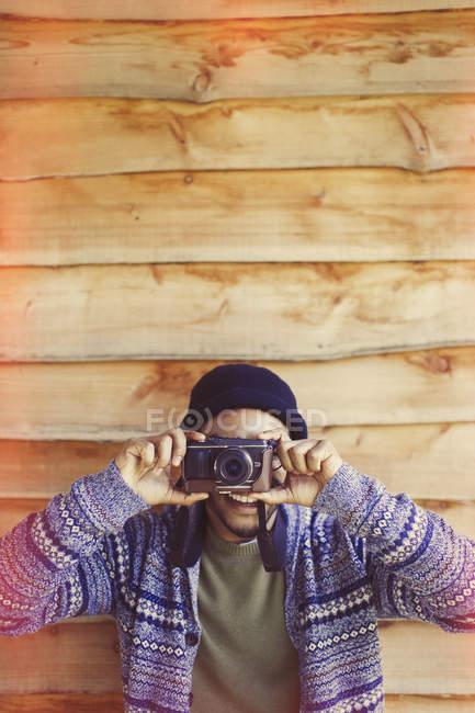 Portrait playful man using camera outside cabin — Stock Photo