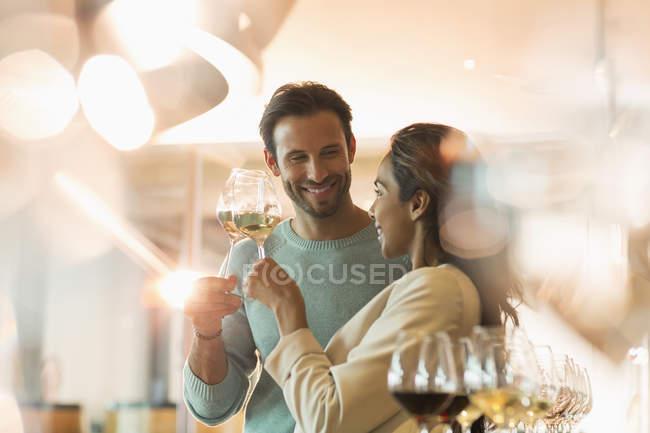 Degustação de vinhos de casal na sala de degustação da adega ensolarada — Fotografia de Stock