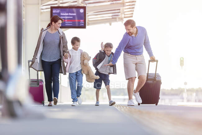 Familia caminando tirando maletas en la estación de tren - foto de stock