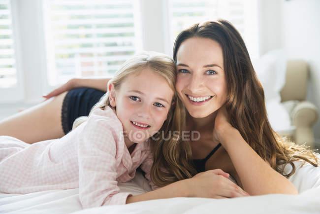 Портрет, посміхаючись, мати і дочка, лежачи на ліжку — стокове фото