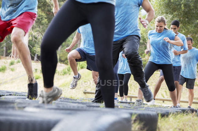 Des personnes déterminées sautant des pneus sur le parcours d'obstacles du camp d'entraînement — Photo de stock