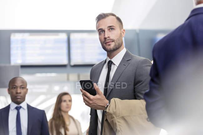 Uomo d'affari con cellulare in piedi in aeroporto — Foto stock