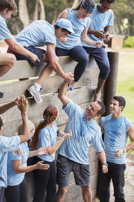 Companheiros de equipe ajudando uns aos outros sobre parede no acampamento de obstáculos — Fotografia de Stock