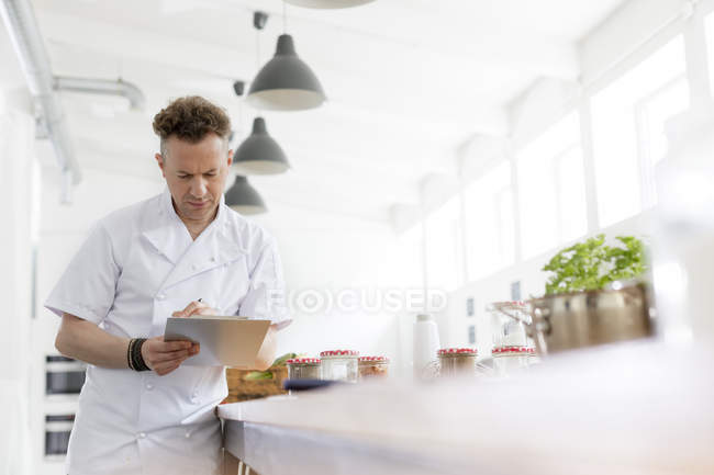 Chef teacher preparing with clipboard in cooking class kitchen — Stock Photo