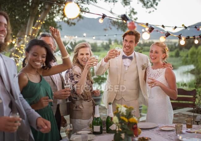 Молода пара та гостей тостів з шампанським під час весілля прийом у внутрішній сад — стокове фото