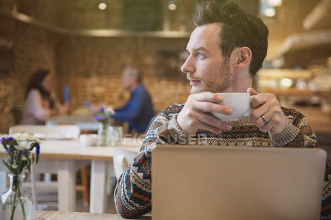 Pensive man looking away drinking coffee at laptop in cafe — Stock Photo