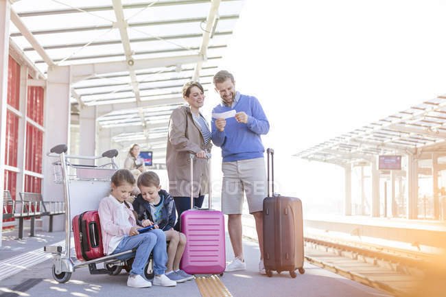 Family with suitcases waiting at train station platform — Stock Photo