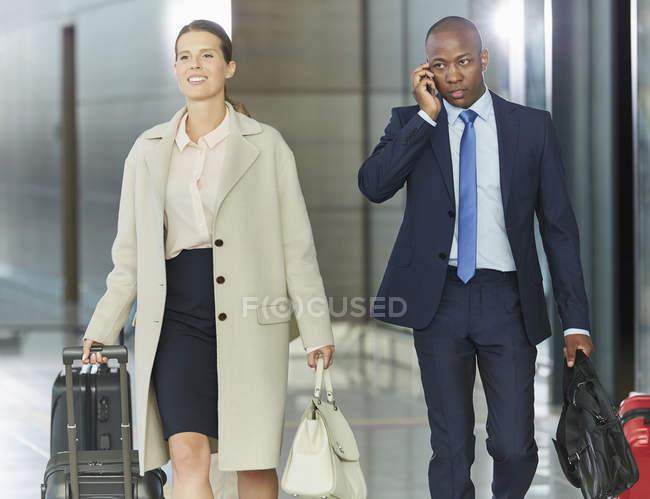 Uomini d'affari che camminano con i bagagli nell'atrio dell'aeroporto — Foto stock