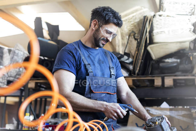 Smiling metal worker using equipment in workshop — Stock Photo