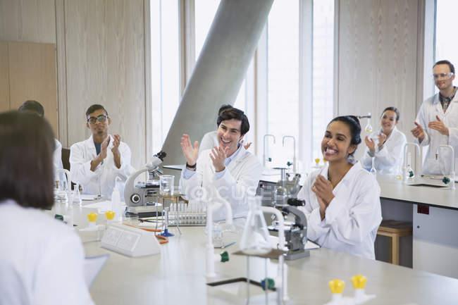 Estudiantes universitarios aplaudiendo a su compañero de clase en el aula de laboratorio de ciencias - foto de stock