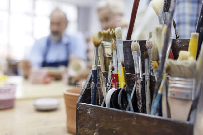 Paintbrushes in box in art studio — Stock Photo