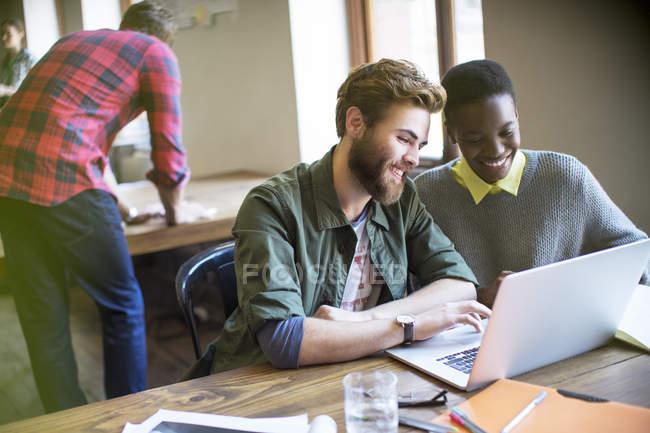 Lächelnde Geschäftsleute, die im Büro am Laptop arbeiten — Stockfoto