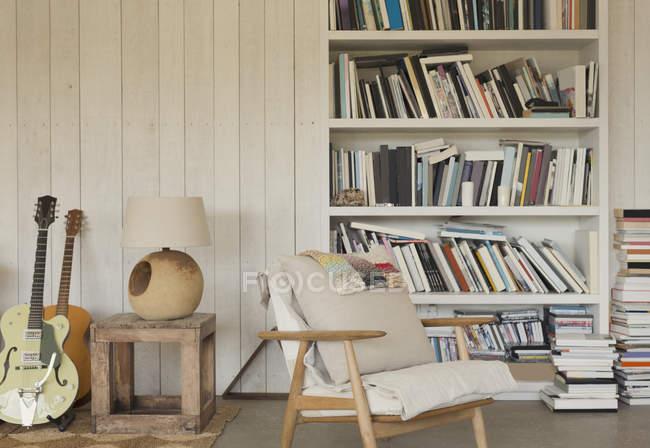 Gitarren und Bücher im Bücherregal — Stockfoto