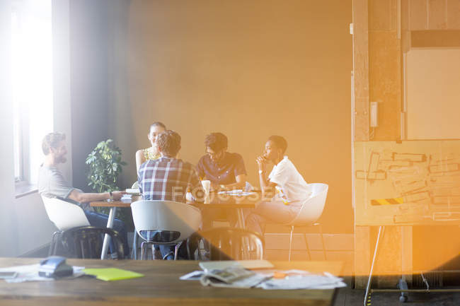 Lens flare over creative business people meeting at office table — Stock Photo