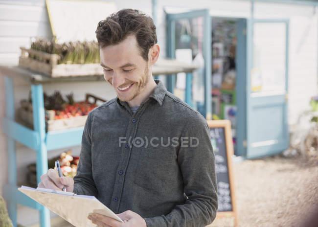Улыбающийся работник питомника с планшетом — стоковое фото