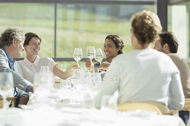 Друзями тостів чарки сонячного ресторану, у — стокове фото