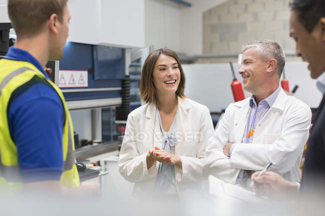 Smiling engineers and managers in steel factory — Stock Photo