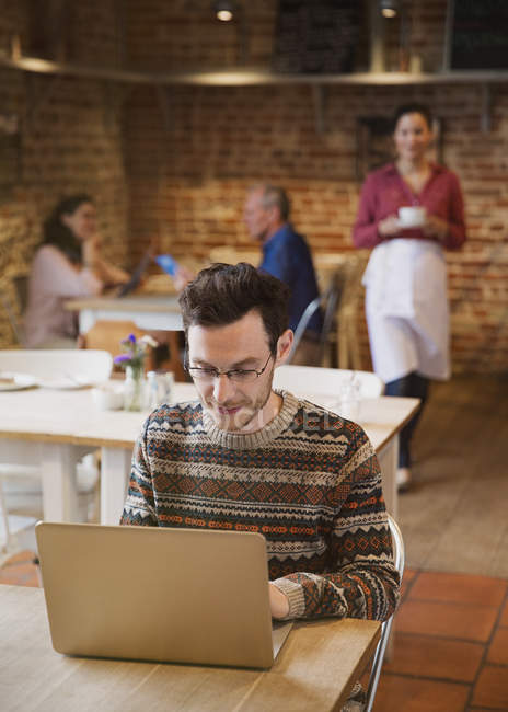 Man in sweater working at laptop in cafe — Stock Photo